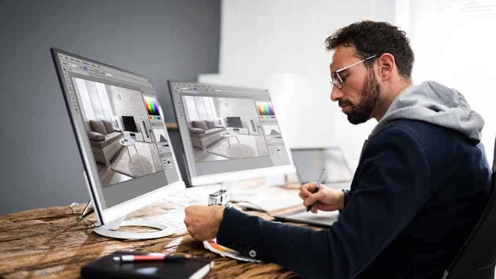 designer editing photos on multiple laptop screens