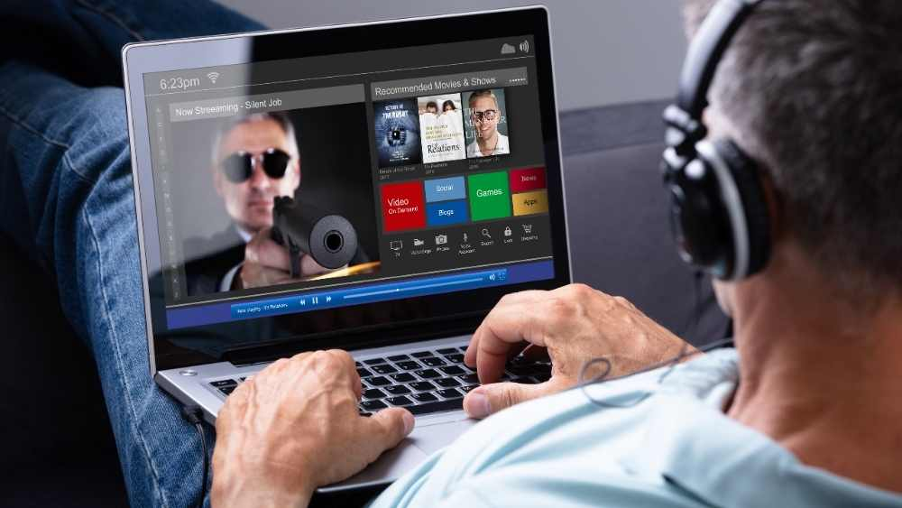 a man watching movie on laptop