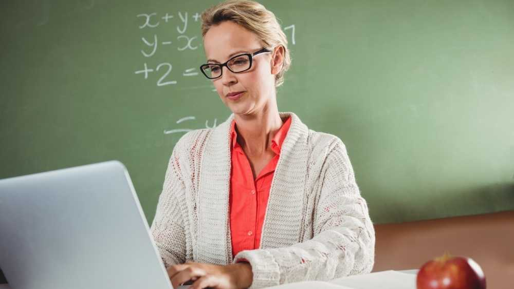 a teacher using her laptop in the class