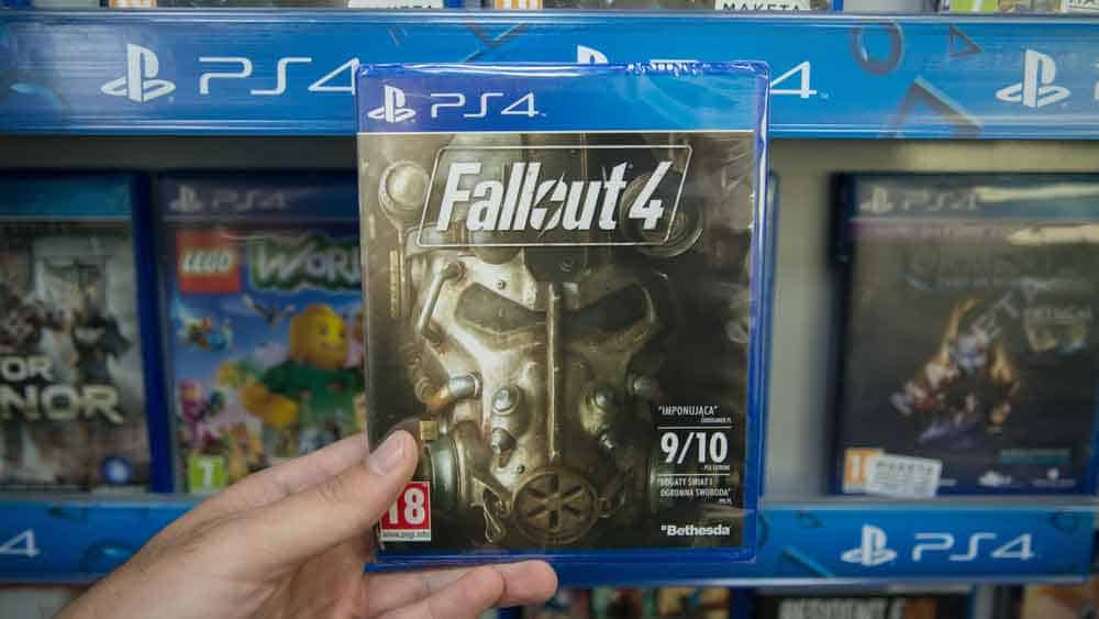 Man holding Fallout 4 videogame on Sony Playstation 4 console in store