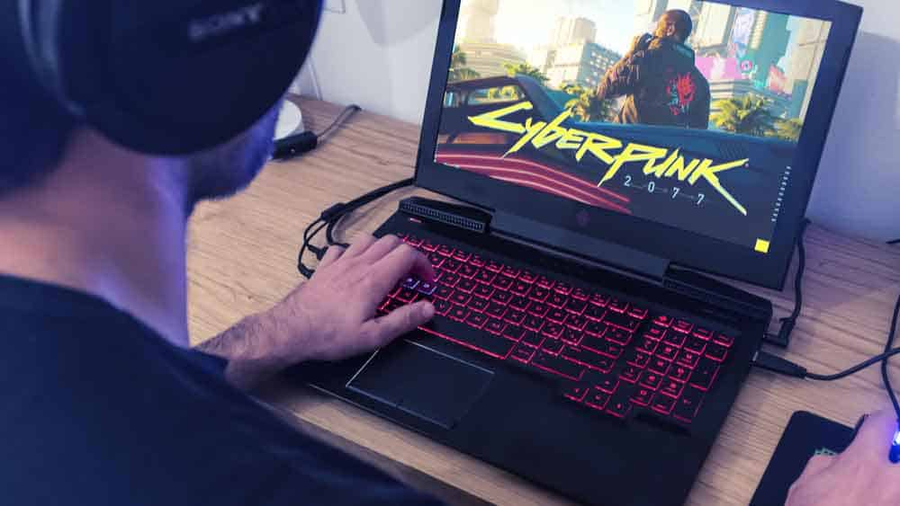 boy playing a videogame called Cyberpunk 2077 on a gaming laptop